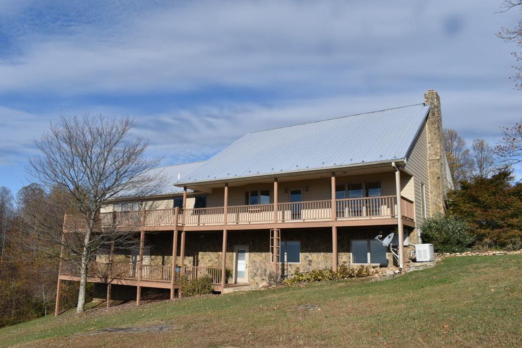 """3.66 acres with a Piedmont View home right off the Blue Ridge Parkway. Home features: 3750 sq. ft., 2 Bedrooms, 3 Baths, You have an open floor plan with a stacked stone gas log fireplace, tongue and grove pine ceilings and walls, tile flooring, Bose sound system with speakers & Yamaha receiver with remote speakers in master bedroom & deck. Large flat screen TV also conveys. Dry bar with ice maker, glass door cabinets and marble counter.  Beveled mirror glass divider in entry hall. Kitchen features: granite counter tops with tile back splash, 48"""" stainless steel Viking commercial gas range with double ovens, grill,  griddle and a Broan hood propane stove. Over-sized refrigerator. Large L-shaped island which seats six and has a prep sink. Garbage disposal. Bay window looking over the Piedmont and access to the rear porch. Large walk in pantry. Laundry room has extra cabinets, shelving and freezer is included. Bath with jetted tub. Enjoy your own study with a built in desk, bookcase,"""
