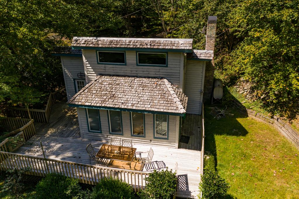 Hunters paradise, outdoor lovers playground!  7 Unrestricted acres down a road that is so beautiful you drive slower just to take it in, not because they're curvy!  You simply cannot help but relax when you go to this gorgeous Grayson County home with Peach Bottom Creek flowing by & amazing mountain views from the top.  There are huge hardwood trees, moss covered boulders, streams, wildlife, & a variety of birds.  Very little lawn to mow, enjoy your time playing, fishing in broad, clean, constant, Peach Bottom creek.  You can hear it splashing over rocks from every room in the house, the decks & the guest house.  There are bridges, boardwalks, trails & boulders all over this property to explore.  The home is filled with natural light from a generous supply of large windows giving it a tree house effect.  The master has a large en suite bath, & there is another half bath for guests.  2 sleeping areas upstairs, 1 accessed via the ladder built into the wall so, yes the furniture stays.