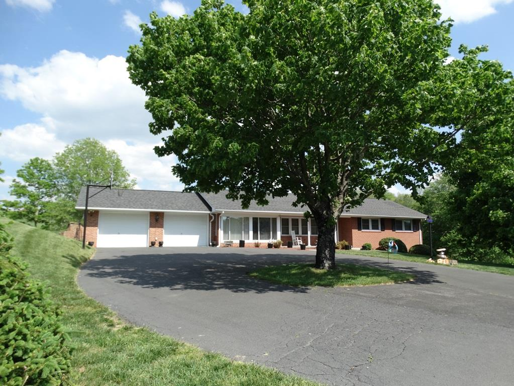 Immaculate home on 5.5 Acres in Fancy Gap! This home has it all! 1785 sq. ft., 3 bedrooms, 1.5 baths, Living Room with new carpet, Large tiled sun room with gas log fireplace, Kitchen with breakfast nook, Dining Room with hardwood flooring and another gas log fireplace, Master bedroom with half bath and new carpet, 2 other bedrooms and bath. Laundry is on the main level. New paint. Double car carport. Full basement partially finished with a oil monitor, wood stove, 2 sinks, shower and refrigerator. Basement could be easily finished. Land features: Fenced pasture land, stream, outbuilding with lean to. An added bonus is a one of a kind Log cabin with wood burning fireplace, one room and loft. This is a beautiful piece of property. Paved drive and Heat pump. Riding lawn mower also conveys. Located less than 1 mile to the Blue Ridge Parkway and I-77. Some of the furniture will convey with the home.