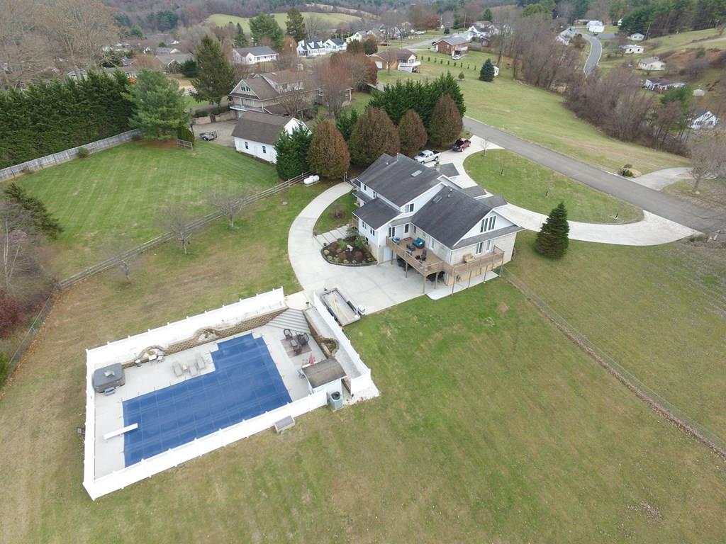 Absolutely amazing custom brick home resting on 1.65 acres in a very desirable neighborhood in the city of Galax. This Immaculent home has many great amenities including 2 full size kitchens, a 3car garage, a laundry room on every level, a large grandmaster suite with large bath, and a heated underground pool. On the main level of this home you will find a newly updated kitchen with stainless steel appliances, granite countertops, a double oven, a breakfast area overlooking the pool area, and a formal dining room. The main level also features 3 bedrooms all on suite with bathrooms, a formal living room, a family room, and a one car garage. The second floor of this home holds the grandmaster bedroom suite with a fabulous master bath. The bedroom measures 151x297 with the bathroom measuring 1111x178 complete with a jet tub and electric fireplace. The upper level also houses a media room, an office, and another bath.