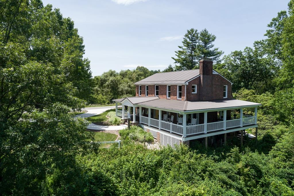 """The Crest at Pipers Gap"" features: 8+ acres adjoining the Blue Ridge Parkway with fenced pasture land, a 6 stall horse barn with new roof, feed room & loft. Home has been totally remodeled and tastefully decorated with 5 BR, 5 BA, 2286 sq. ft., Walk into the foyer from the 936 sq. ft. new, 12 ft wide covered front and side porch with long range countryside and mountain views. Home comes mostly furnished (excluding the bird's eye maple bedroom set and antique bedroom dresser). On the main level is a living room with a gas logs or wood burning fireplace, a spacious dining room that leads out to the covered side porch, kitchen, bedroom with a walk in closet, full bath and a spacious laundry room and office. On the upper level you have 3 master bedrooms with full bathrooms in suite, the 4th bedrooms bathroom is in the hall.  New concrete circle driveway and walkway with a large area for parking. Newer metal roof, 2  heat pumps with gas pack, wood stove in full basement,"