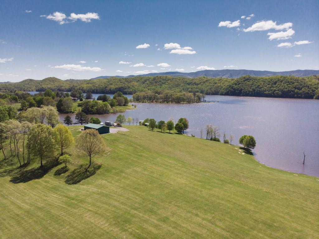 On the sparkling banks of the main waters of beautiful South Holston Lake lies this incredibly unique and rare property which is entering the real estate market for the first time!  Offering majestic views of the Cherokee National forest mountain range, this 22.95 +/- acres boasts amazing home sites with level and slightly sloping land rolling softly to the edge of the pristine waters of the lake.  As much of the shoreline of South Holston Lake borders the national forest, main water acreage such as this is extremely scarce!  Easily accessed by a state/county road and neighboring the shores of lovely Camp Sequoya, this amazing open land can be whatever your vision desires to make it!  Already in place is a 30' x 50' garage with double doors and single entrance, a 20' x 40' picnic shelter, an aluminum boat slip with steel poles and a wooden dock directly on the lake, and a covered camping station with a deck facing the spectacular water & mountain views!