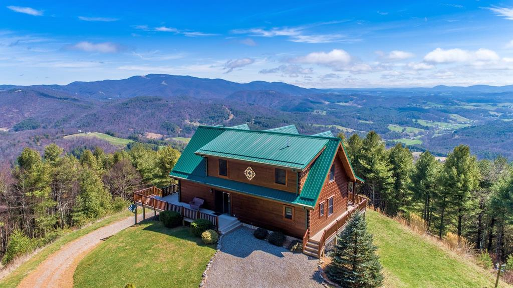 Majestically sited at the end of the road on a rambling 22+ acre setting high on Kindrick Mountain with panoramic long range mountain vista views, this fabulous 3-bedroom, 3.5-bath Jim Barna log home demonstrates the perfect blend of sophisticated and casual elements as well as quality materials and craftsmanship. Meticulously cared for and maintained, this property embraces privacy, seclusion, and Nature's beauty. The main level offers an open great room with soaring vaulted ceiling, 2-story stone fireplace with gas logs, gleaming wood floors, stunning architectural accents & custom appointments throughout the home. Other features include a well appointed kitchen with custom cabinetry, granite counter tops, large pantry, & bay window to enjoy the views; main level master suite, powder room, easy access to the partially covered deck & exquisite long range views.  The upper level offers a loft area, guest bedroom & full bath.