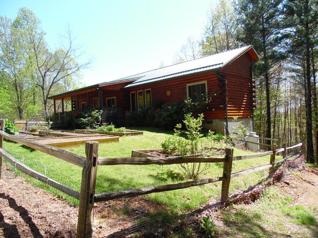 Exceptional log cabin with just over 8 acres in the Blue Ridge Mountains near Chestnut Falls.  Spacious front porch, sun lit indoor space feels welcoming with floor to ceiling stone gas log fireplace and a stunning open floor plan, beautiful kitchen with plenty of cabinets. Primary living area on first level. Gleaming hardwood floors including maple, Brazilian cherry and oak.  Three full baths, 2 on the main level and one in the 450 square foot finished portion of the basement.  Ample storage with large closets and outbuildings with space for your cycles and kayaks, a home workshop/office on the lower level. The 8.51 acres include flower beds, gardens, fruit trees, blooming perennials, and three springs...just minutes to the New River Trail access located in Carroll County, VA  Perfect for nature lovers and outdoor enthusiasts, check it out today! Recent upgrades include a gravel walkway to backyard, a greenhouse, move-in ready!  HOA $350 annually