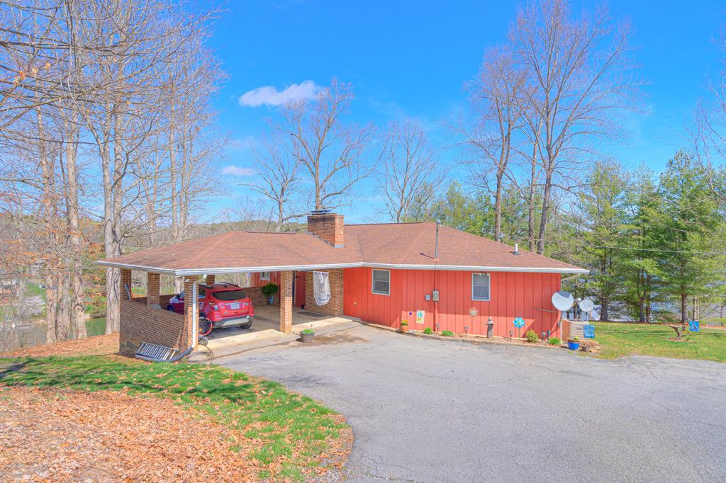 Check out the video and 3D tour!! 137 ft waterfront. Walk right into beautiful large great room that looks right out to the lake. Hardwoods throughout. Gas fireplace. Spacious screened in porch spans the entire front of the house. 2 lg MBdrm suites on this level, one with 8 feet of sliding glass that walks right out to a private deck. Upgraded kitchen with newer appliances, lots of cabinet space, a roomy pantry and built in shelves. Head downstairs for a cozy paneled family room w/ gas f/p; walk out to covered patio. 2 more large bedrooms, a den, a storage room, and a large workroom with laundry access. Head outdoors ... the stairs and several levels of gorgeous deck and entertainment space leading down to the lake front are truly a lake-lover's dream! Completely covered new (2018) double-tiered boat dock with lift, swim platform and large upstairs deck with gorgeous lake views. Sheltered cove area. Room to host family, friends and fun; you'll never have to leave to vacation again!