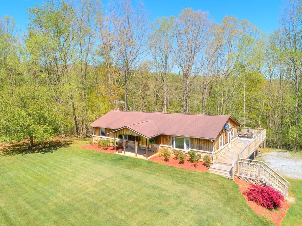 This private ranch home on over 2 acres of property is a peaceful rural retreat!  The rustic wood siding and wrap around porch, along with the beautifully maintained landscaping will catch your eye! Enter via the side door on the wrap around deck right into the kitchen. All stainless appliances, lots of counter and cabinet space. Full sized dining room with a large bay window flows right into the cozy, custom paneled living room, makes entertaining easy! The large family room/ recreation room on this level, also beautifully paneled, opens onto the spacious deck! Three carpeted bedrooms, with roomy full baths in both the hall and Master Bedroom. Master has a cedar lined wall sized closet. The basement includes the one car garage; the rest is partitioned into a partially finished rec area, laundry and utility area. Head outside for an adventure in bordering Tom's Creek,. Fishing fans will want to find the trout that are released just below this property. A country living must see!