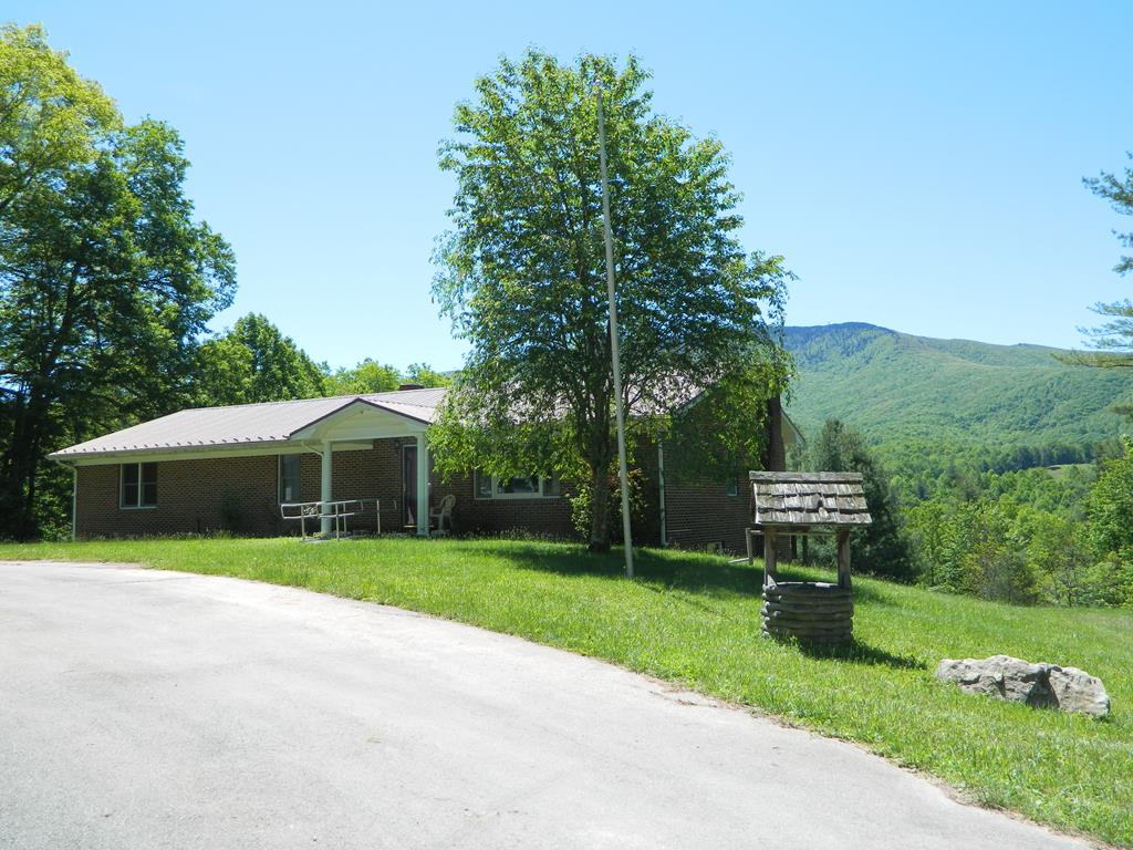 VERY PRIVATE...FANTASTIC VIEWS OF WHITETOP MOUNTAIN...1 ACRE OF LAND... come with this beautiful 4 BR, 3 BA brick ranch. Views of only the mountains from this house - no close neighbors. Main floor overs large eat-in kitchen with bar seating, granite countertops, pantry, 3 bedrooms, 2 baths. Huge owners suite with private bath (tub/shower) enclosure and laundry room, spacious living room and large foyer. Walkout basement feature family room with stone fireplace, large bedroom, full bath and plenty of storage and/or workshop area that could be finished living space. House has heat pump. Old boiler and registers still in place, but needs repair to be operable. Great views from the back deck. Outbuilding for storage. Two car over-sized garage with electric door openers. Paved drive. Deeded access to property.