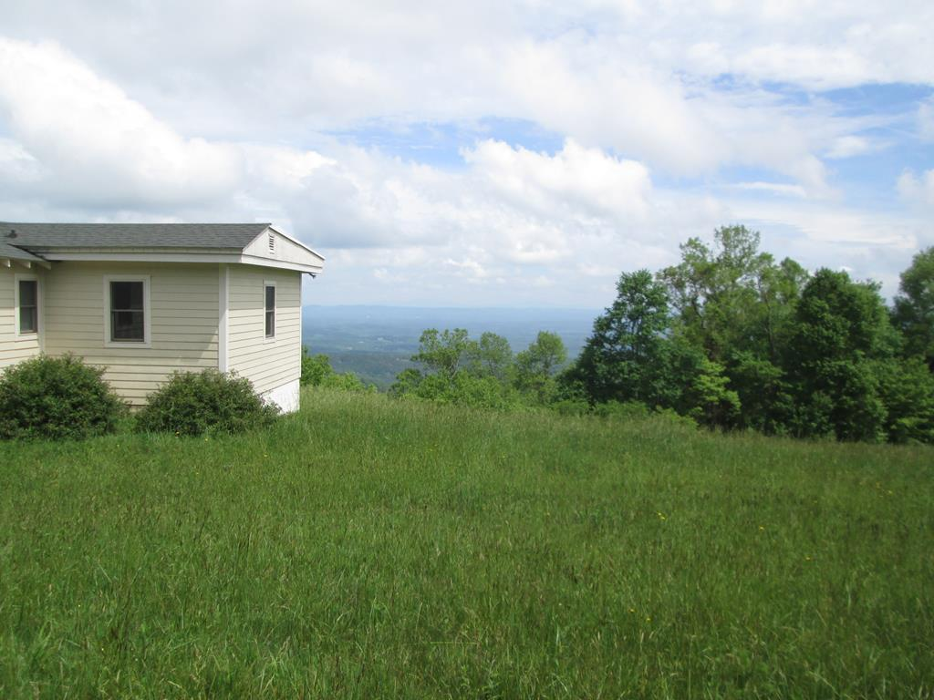 2 Cabins (one authentic log) on 72 acres overlooking the Piedmont. Perfect 2nd homes or vacation rental investment property. Approx. 10 acres cleared and grassed all with views of the Piedmont. Remainder of land in woods. Located just off the Blue Ridge Parkway- easy level road to property.