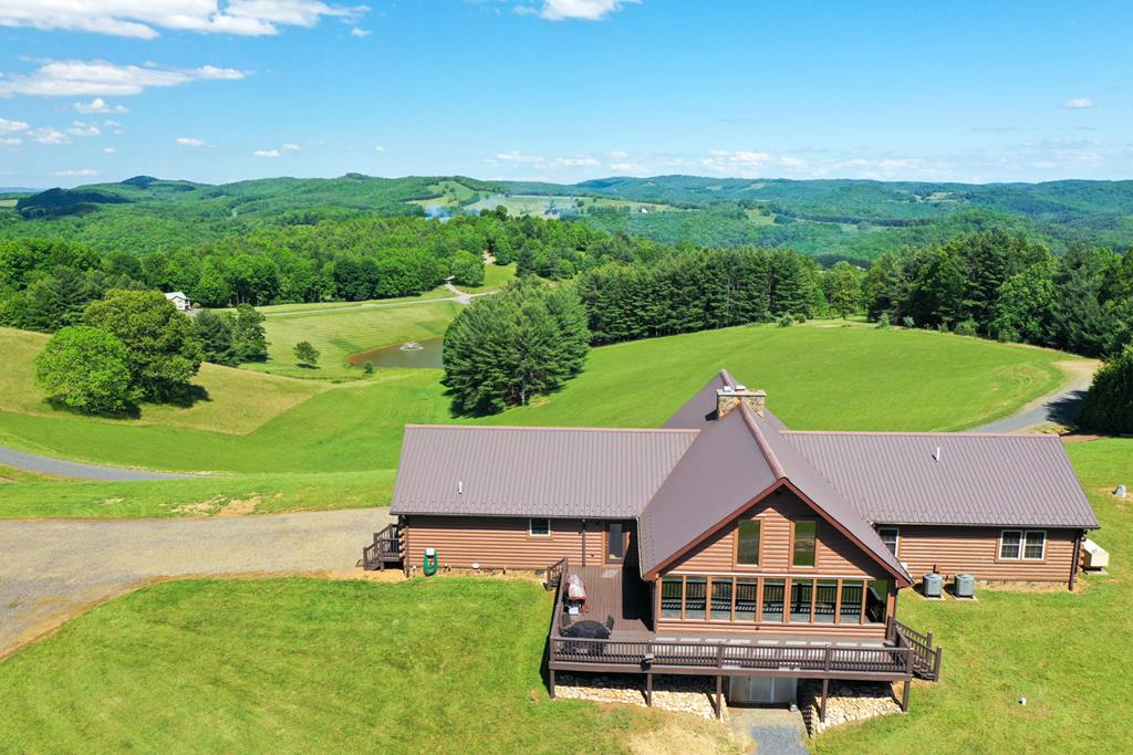 STUNNING CUSTOM BUILT LOG HOME WITH PANORAMIC 360 DEGREE VIEWS! CAREFULLY CRAFTED AND WELL MAINTAINED HOME RESTING ON 30 ACRES OF OPEN AND WOODED LAND! BOASTING A SPACIOUS OPEN FLOOR PLAN WITH SOARING 20 FT CEILINGS IN LIVING AREA AND SUNROOM WITH DOUBLE SIDED FIREPLACE. GREAT FOR ENTERTAINING OR JUST HANGING OUT WITH THE FAMILY. FEATURING 3 BEDROOM 2.5 BATH, KITCHEN WITH CUSTOM CABINETS, LAUNDRY AND 2 CAR GARAGE ON  THE MAIN LEVEL. FULL FINISHED BASEMENT  WITH LARGE LIVING AREA, ROCK FIREPLACE, 2 BEDROOMS, FULL BATH AND GAME/ WORKOUT AREA. HOME IS EQUIPPED WITH WHOLE HOUSE GENERATOR. NICE DETACHED WORKSHOP. EXPANSIVE BACK DECK IS GREAT TO TAKE IN THE LONG DISTANCE VIEWS AND EVENING SUNSETS THAT SET A PEACEFUL TONE! THE FAMILY WILL ENJOY THE LARGE STOCKED POND WITH DOCK AND GAZEBO. ABUNDANCE OF TROPHY SIZE WILDLIFE OF WHITETAIL DEER AND TURKEY. SHORT WALK TO SOME OF THE BEST TROUT FISHING IN THE BLUE RIDGE MOUNTAINS AND LOCATED WITHIN MINUTES OF GALAX AND I-77.