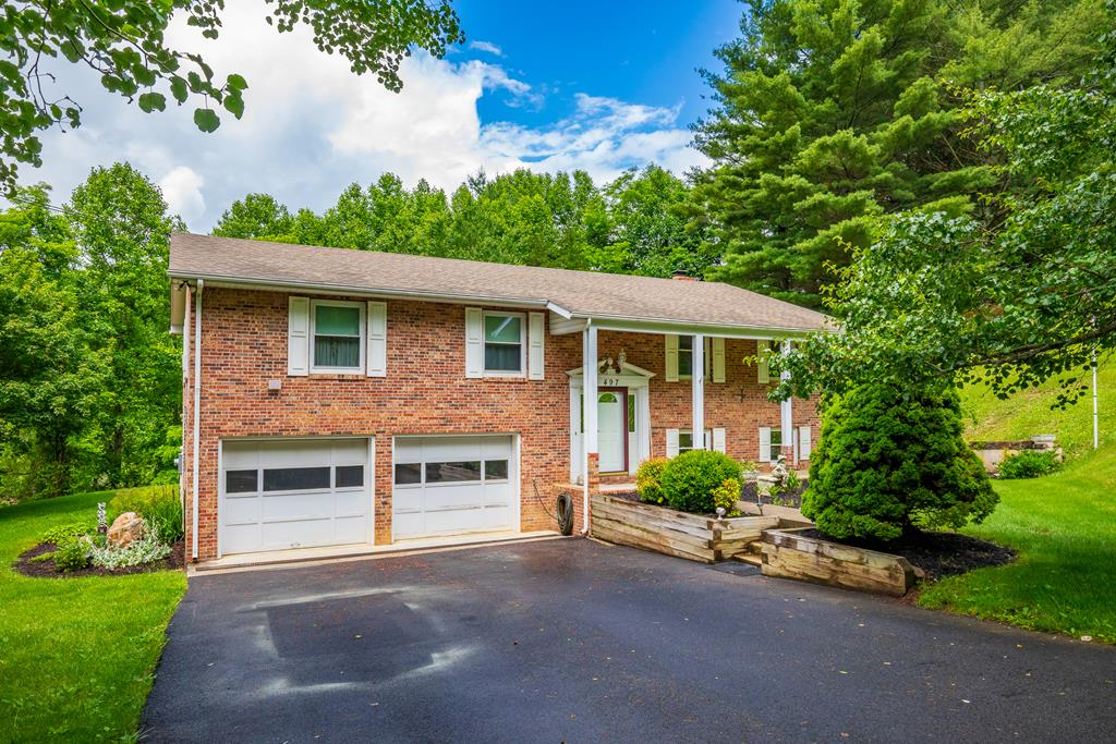 Gorgeous 3 BR 2.5 BA split level home on about an acre in Deer Run Estates in Rocky Gap, VA. 2 car drive under garage and nice lot with quality landscaping. Main level includes all three bedrooms and features a large master suite, the living area, separate dining room and kitchen, and even a sunroom that is connected to the rear deck. Downstairs you'll find the half bath, entranceway to the garage and laundry area, and two large rooms which both would be perfect for a number of things such as a man cave, play area for kids, exercise room, or even a potential 4th BR or den. The largest of the two has a wood burning fireplace and sliding glass doors that lead to the patio. Other features include carpet, vinyl, tile and new laminate wood flooring, tilt windows, fresh paint, a remodeled second bathroom, a new Samsung refrigerator and KitchenAid dishwasher, a 12x20 outbuilding with roll up side entry doors, a new 200 amp breaker box in the house, and boasts well over 2100 sq. ft. finished!
