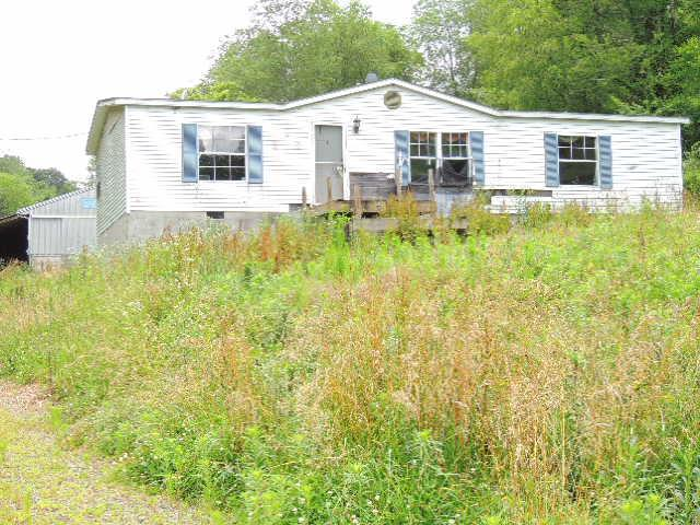 CHECK OUT THIS 84+ ACRE TRACT OF LAND. PROPERTY FEATURES A CREEK, LARGE  1200 SQ. FT. BARN, SEVERAL OUTBUILDINGS, SOME FENCING, APPROX. 70% WOODED. DOUBLE WIDE HOME TO CONVEY AS PERSONAL PROPERTY BY MEANS OF A BILL OF SALE.
