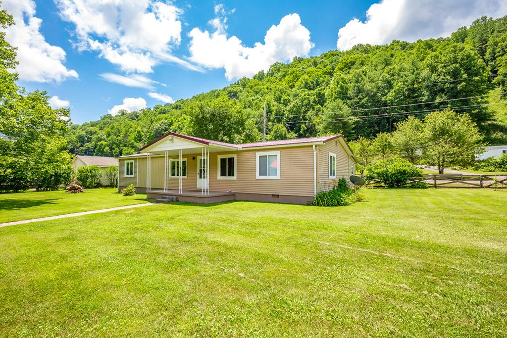 3BR 2 BA Doublewide on a permanent foundation in Rocky Gap, VA. This mostly remodeled home sits on 2 level lots with a commercial size garage (220 elec.), small storage building, and a larger storage building with a root cellar. Paved driveway with a triple carport, and LOTS of upgrades. New metal roof approx. 2 yrs old, new gutters, new deck, some fresh paint, new french doors, new front door, new picture window, some new interior doors, and all remodeled rooms were upgraded with sheetrock. Heat pump/central air, and a fireplace with gas log insert. This is a must see and overlooks Wolf Creek. Includes apple, pear, and cherry trees, in a quiet neighborhood, extra parking, just 1 mile off of I-77 and approx. 13 miles to Princeton or Bluefield. Conventional financing or cash only.