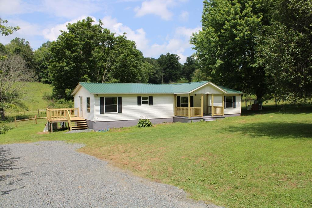 Newly remodeled double wide home on 0.75 of an acre. Updates are: new roof, A/C, porch, cabinets, appliances, flooring, commodes, windows, sliding doors, and paint. This home has 3 bedrooms 2 full baths and 1456 square feet, large open living room with wood burning fireplace, large kitchen with dining area, master bedroom has a walk in closet, master bath has a garden tub and shower, the 2 other bedrooms have walk in closets also. 2 new porches, one covered,  one open and a back deck. New survey. Located 2 miles from I-77 in Fancy Gap.