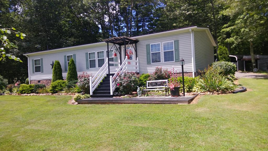 Just 7 miles north of Fancy Gap and 1+ mile off the Blue Ridge Parkway. You'll go WOW! Pride of ownership says it all. Extremely well kept home. 3 Bedroom 2 bath split plan is an ideal layout for any family. Check the kitchen out with lots of storage and custom island. Appliances include Range, Microwave, refrigerator and raised dishwasher for easy access. Hardwood floors in living room and hall. Super master bath with double sinks, deep tub and seperate shower. Walk in closet. NO RESTRICTIONS HERE. Room for motor home or travel trailer. Super nice landscaping. 3 very nice storage buildings  plus 2 carports. You must see this to appreciate just how well maintained it has been kept. Newer Trane heat pump, metal roof, vinyl siding all say low maintenance. Outside kennel for Fido is you need one. Peace and serenity. Listen the the birds sing and watch wild life go ambling by. 12 minutes to Fancy Gap. 25 minutes to Mount Airy. About 4 minutes to the Blue Ridge Parkway.