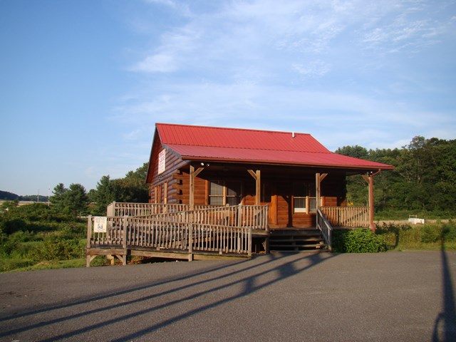 Log cabin is right in sight of I-77 in Fancy Gap. Cabin can be used for a home or a business. Home features: 1608 sq. ft. Great room on the main level with an open living room and kitchen, Gas log fireplace, 2 Bedrooms on the main level and a room that is being used as a bedroom on the lower level. 2 Baths - one on each level. The lower level has an open living room and kitchen also. This property could be used for your business, home or rental property. Great location and opportunity. Located one mile from the Blue Ridge Parkway.