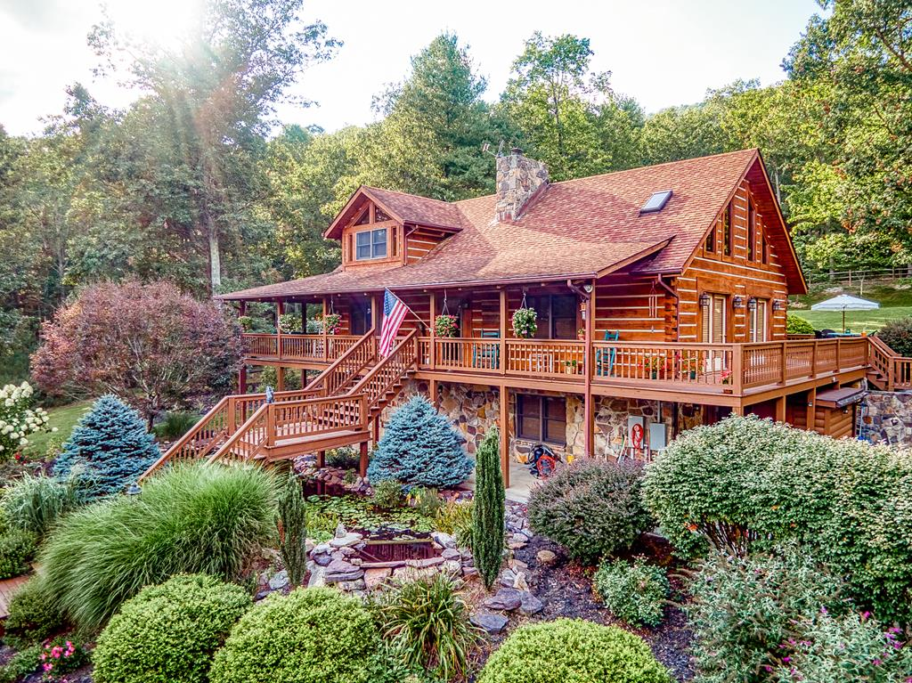 Take a look at this stunning custom log home built by Appalachian Log Structures Inc. Follow the 1/4 mile paved driveway to your own private mountain retreat totaling 452 acres +/-. This property offers a 3,265 sq ft home with 3 BR's and 2.5 baths, a 936 sq ft custom log cabin at the top, beautiful fish ponds and landscaping, numerous outbuildings, fenced in backyard, a concreted & fenced area w/ roof for your dogs, an artesian well, Corian countertops in the kitchen and a full wrap around porch which is covered on the front and one whole side. Both the log home & log cabin have home generators. This is a once in a lifetime property and is perfect for the outdoorsman as you are surrounded by many ATV trails and an abundance of wildlife. The views from both the home and from the cabin are breathtaking so DO NOT miss your chance to own this unique and gorgeous property! Call today for your private tour!