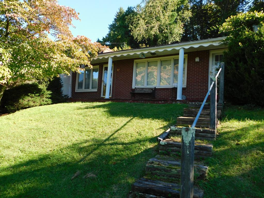 This nice brick ranch style home situated on Surface Drive almost gives you a birdseye view of main street Tazewell! You will love the convience of this home allowing you a short stroll to Historic Downtown. This home can be made to feel warm and cozy with just the right visionary. The family room offers a gas log fireplace, built in shelves and terracotta flooring. The large living room, kitchen and dining room have beautiful hardwood floors. The sunroom, just off of dining room has brick floors and floor to ceiling windows. Just off the spacious master bedroom is a 11x9 master bath with Jacuzzi tub and step in shower. There are permanent stairs to a partially floored attic. The basement will allow for plenty of storage or a hobby room. Bring your creative ideas and start getting this jewel ready for the holidays just like grandma use to!