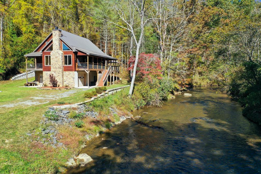 WOW! 1/2 mile creek frontage adjacent to New River trail with gorgeous 3000+ sq.ft. home overlooking the loud stream! This kind of property, almost impossible to find! Great potential camp ground with power already installed or executive retreat.   *Aerial video attached to MLS