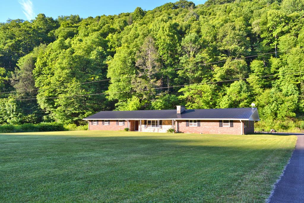 Enjoy the beauty of the country in this rambling ranch style home cradled in a spectacular 5+ acre creekfront setting in the Grayson Highlands. This home offers room to roam with one level living, handicapped accessible, and located just minutes from Grayson Highlands Park, horse trails, the New River, and other High Country destinations.  Currently set up with 5-bedrooms and 2-baths, this home has many possibilities. The floor plan includes a spacious living area with a unique stone wood burning fireplace as its focal point, a generously sized kitchen with informal dining area, a bonus room suitable for 5th bedroom, office, studio, or home gym, and 4 bedrooms, 2-baths, laundry & utility room.  All handicapped accessible with updates that include new flooring in most rooms, updated plumbing, metal roof, & more.  All of this and situated on a 5.299 acre setting on the banks of Big Wilson Creek with big level lawn, garden or pasture area for your horse, and woodlands full of wildlife.