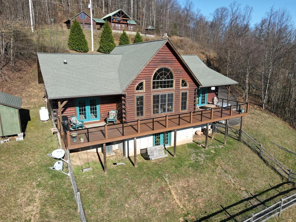 Log home with a 60 mile Piedmont View! Home features: 2280 sq. ft. 2 bedroom, 3 baths. On the main level you have an open floor plan with cathedral ceilings and an awesome view of the Piedmont! Living room has a stone gas log fireplace that also shares with the master bedroom, kitchen has granite counter tops and the table conveys with the sale, a master bedroom that goes out to the open deck, bath with double sinks, jetted tub, shower and the laundry. An office area that also opens up to the Piedmont View, another bedroom and bath. On the lower lever you have a family room with a gas log stove, another room used as a 3rd bedroom and a full bath. utility room/workshop and a 2 car garage. Trex decking in the whole width of the deck. House is wired for a generator. Also, 50 amp RV plug in at driveway. Pella windows, Downstairs opens outside to a fenced in area, great for pets.. You can also walk out to a fenced in and swing area.  12'  x 16' Outbuilding.