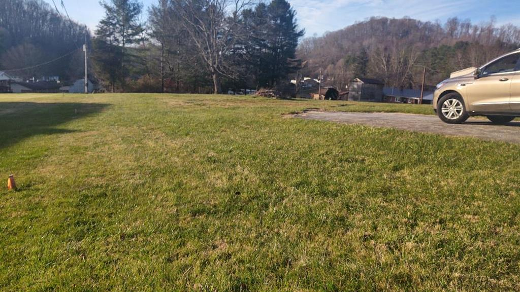 Beautiful level lot...just outside town limits with all the town amenities! Nice lot ready for building or new doublewide home.  New survey with boundary marked. Town water, sewer, paved drive ~ Ring in the new year in your brand new home!!!   The empty trailers across the street are being removed.