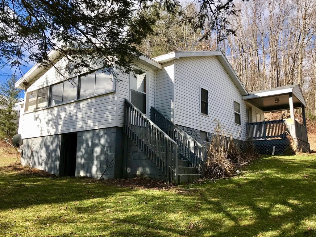 Versatile mountain getaway with tons of potential.  This listing on 3.62 acres needs some TLC but it is priced well below tax assessment and there's plenty of opportunity for upgrades.  The property lies on both sides of the road.  One the main house side you have the house, a large covered garage/shed and acreage to get out on and enjoy.  Across the road, the property borders Laurel Creek along a nice level lot with its own power, well, and septic.  The main house needs some repairs but could be brought back and enjoyed as your mountain home or getaway.  The acreage across the road currently has an expanded single wide (SW with a large addition) sitting on it and, with renovations, has the potential to be a source of rental income or a second home for the buyer. Two homesites (power/well/septic), 3.62 acres, creek frontage, and a large garage/shed-a lot here for the money!