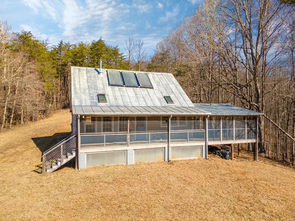 """If you've been looking for a long-range view & water, then this is the perfect property for you! Located in the Woolwine community of Patrick County with elevations of 1,600-1,800 feet. Located about 2.5 hours from Charlotte & the Triangle area of NC & about an hour from theTriad. This amazing 143.7-acre compound only about 16 miles from Floyd, VA. This property has one of the best views of Bull Mountain. that you will ever find. The updated """"industrial farmhouse style"""" has 2 bedrooms and 2 baths. The home has new plumbing, wiring, well, & septic. It overlooks the spring-fed pond, perfect for swimming & has a spectacular long-range view. The property is very private & there are many building sites where you could build another home. Bold streams, springs, & mountain breezes await you at this one of a kind property."""
