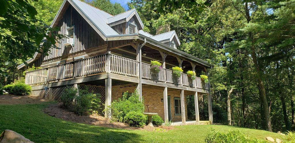 Cabin w/ Long Range Piedmont Views. Located just off the Blue Ridge Parkway, this 4 bedroom 3 bath log home has hand hewn logs, 2 wood burning fireplaces, covered porches and open deck, privacy and an awesome view! You will warm right up upon entering this cozy cabin. There is a mudroom, open living area with vaulted ceiling and bonus area and master suite upstairs, recreation area or den downstairs complete with it's own fireplace and walkout access. This property consists of 3 tracts that protect your viewshed and provide lot's of privacy. Abundant wildlife and recreational opportunities, the community has a heated pool, club house, tennis courts, basketball courts, picnic shelter and common area with pond. Convenient to the Blue Ridge Music Center and not far from the New River Trail and Galax Virginia, there is always lots to do. Relaxing on the front porch taking in the quiet, nature and view is a great plan too!