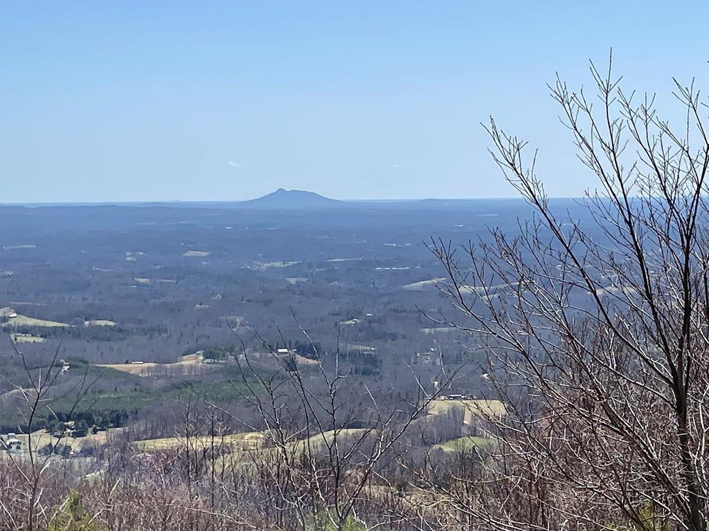 Build your Dream Mountain home  here!  Spectacular full views of the Piedmont with direct view of Pilot Mountain and Winston Salem lights! Beautiful for all seasons.   Flat driveway access possible from Reflection Point Trail.  Large out crop of Rocks  which would make a loving homesite to build.  Approximately 1.4 acres with a 60+ mile distant views.  Your investment is protected here with covenants to maintain the aesthetics! Roads are all paved to this location.