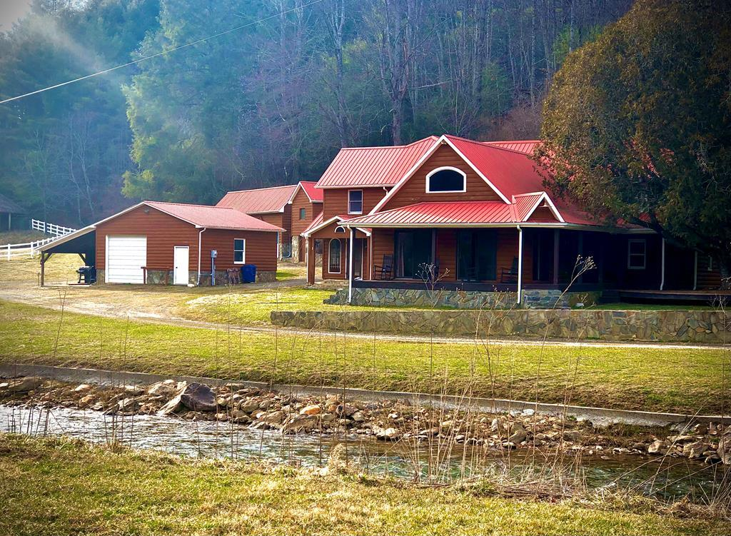 Equestrian paradise on Big Reed Island Creek. Ultimate custom home & guest cabins loaded w/amenities. The wrap-around porch leads to the main entrance, and steps in to a fabulous Great Room with a 20 foot vaulted ceilings, stone fireplace, beautiful hardwoods, and a full-sized bar, complete with an industrial under-bar cooler, and exposed beams. The kitchen and dining area has 2 double stainless steel refrigerators, a gas cooktop/ grill/griddle, wood cookstove,  industrial and standard sinks, wall oven, and an electric stove, with infinite oak cabinetry. The master bedroom features a sitting room with tray ceilings, and a gas fireplace, in-laid hardwood floors, and a 18x21 master bath with a jetted tub, bidet, full-sized shower, a separate water closet, and a huge walk-in closet. The main level also has a cozy den with a stone flue and pellet stove, 2 full bathrooms, a utility area, and a large main level bedroom. Upstairs find 2 more spacious bedrooms & full bath.