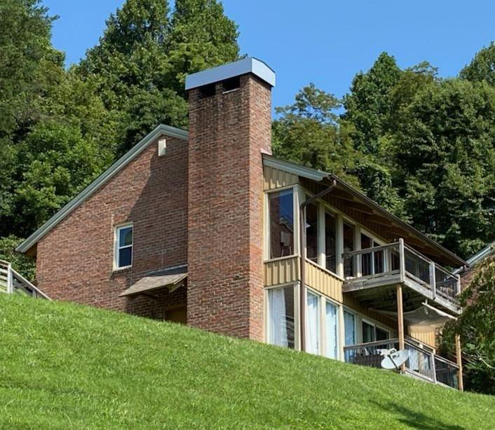 Upper level tennis chalet at Doe Run/Groundhog Mountain with gorgeous views in every direction you look.  New HEAT PUMP (only 3 hours usage).  The great room features a wall of windows to bring those gorgeous views right inside with you .  The brick wood-burning fireplace makes the main living area a cozy retreat on those frosty mountain nights.  A cathedral ceiling makes the living area seem large and spacious.  There is even a small loft with room for 2 twin beds.  The kitchen and dining area complete the great room area.  There are plenty of cabinets and storage in the kitchen.  There are 2 bedrooms of the same size with matching bathrooms and closets.  One bedroom has a stack washer and dryer unit.  The home comes mostly furnished and it's move-in ready just in time for you to enjoy the end of summer and those gorgeous leaves in the Fall.