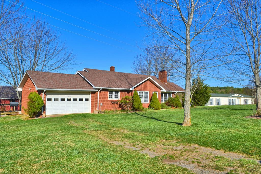 Sweet farm property with two homes and 10 beautiful acres just off the Blue Ridge Parkway in the Hillsville area of Carroll County.  First home is a 2-bedroom, 1-bath brick ranch style home with 2 car attached garage, hardwood floors in living room and bedrooms, parquet in dining room, ceramic tile in the kitchen and bath. Fireplace with wood stove insert in the living room. Full unfinished basement offering tons of storage space and a great place to can your garden harvest. With some fresh paint, updates, and your personal touches, this could be a fabulous home. The second home is a well kept 3-bedroom, 2-bath 2008 Clayton doublewide with carpeted and vinyl floors. The acreage is picturesque with garden space, barn, outbuilding, lush green fields, and gorgeous pastoral and mountain views.  The location is just off the Blue Ridge Parkway. This property is ideal for those looking for farm property, a place for extended family, or investment property.