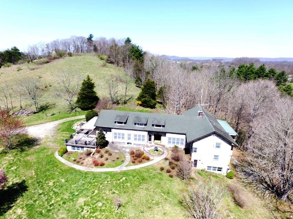 Massive home with fine finishings settled on a ridge overlooking Reed Creek on 8+ acres in Wytheville, VA is available priced well under tax assessment. With 8 bedrooms and 6 bathrooms and large gathering spaces inside and out, this home has had some significant recent renovations that preserve the amazing character of this chalet like setting which is highlighted by the hardwoods and the cathedral-like family room complete with stone fireplace. With views of the mountains and overlooking the acreage, this beauty has lots of glass and other cool features like a ramp system from floor to floor to avoid the need for stairs allowing easier access to the entire house. There's entertaining space inside and out and with multiple screened-in porches, there's room for hosting large events. The property is zoned agriculture so bring the animals to roam on the acreage. Within a few minutes to both I-81 & I-77 as well as downtown Wytheville, this property is a hidden gem with lots of benefits.