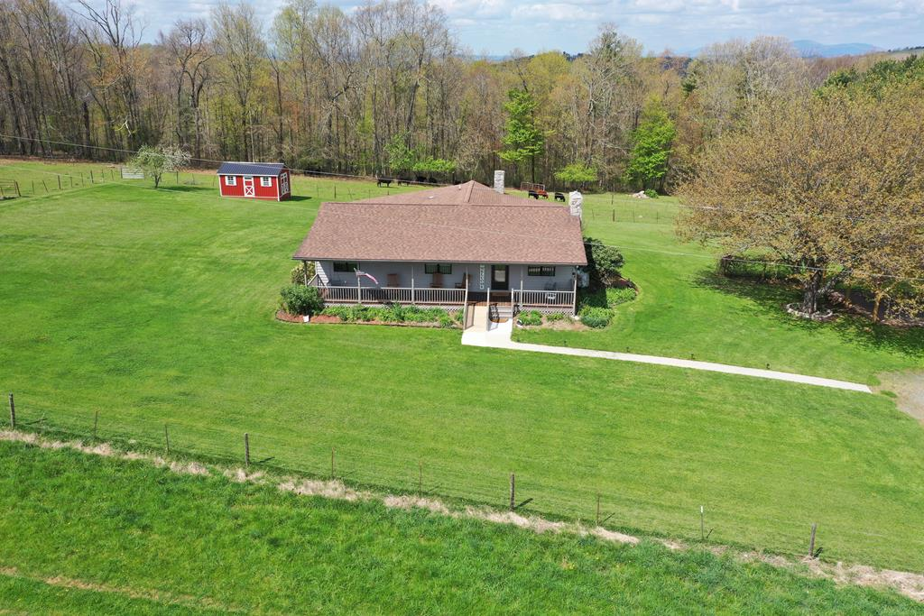 Amazing 90 acre cattle farm! This property offers a one level, 4 bedroom,3 full bathroom home completely renovated and comes completely furnished. Beautiful hardwood flooring ,eat in kitchen with major appliances, as well as a large open living dining combination that boasts of rustic with beamed accents and stone wood burning fireplace. All three bathrooms have been updated with new vanities, tile showers and flooring. Partially finished basement has a den and kitchenette. Exterior amenities include two covered porches, an open deck, multiple sheds  and timber/paver carport. There are two large barns and one shed barn at the back of the property. The acreage is partially wooded and has approximately 60 acres of beautiful rolling pasture with the entire perimeter fenced with high tensile, an abundance of water with three streams and five water troughs for livestock.Gorgeous long range views from property. A few miles to the Blue Ridge Parkway and City of Galax.This property has it ALL!
