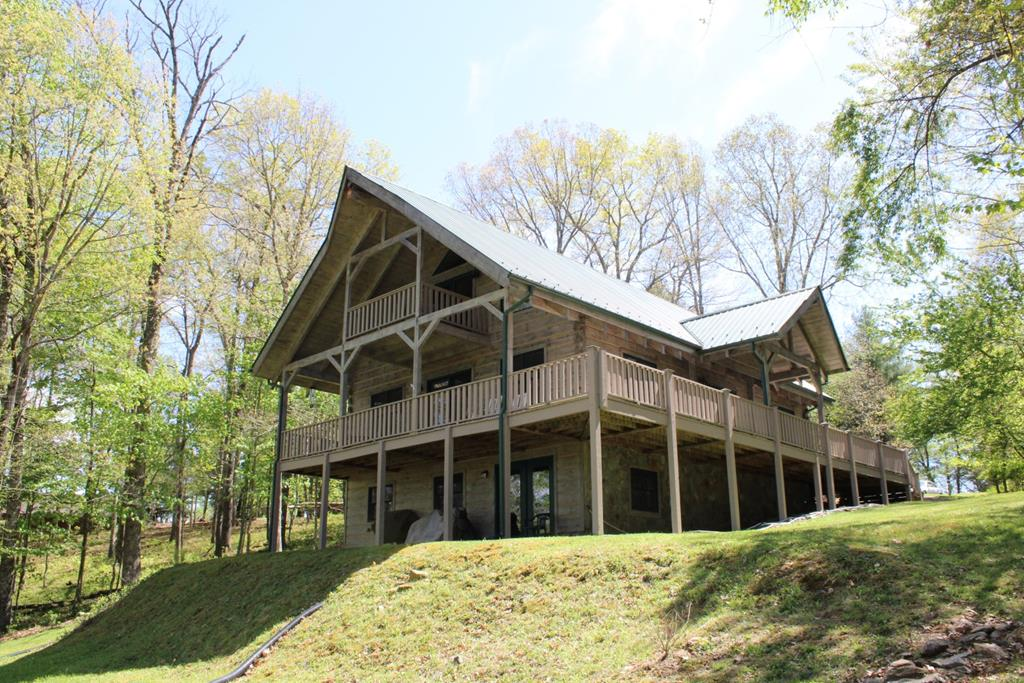 Custom built log home adjoining Olde Mill Golf Course. Home features: 1944 sq. ft. 3 bedrooms, 2 baths. Ceiling beams and hardwood flooring throughout home. On the main level you have an open living room, dining room and kitchen with granite counter tops and all appliances conveying, 2 bedroom, 1 bath and a laundry room. On the upper level you have a huge master bedroom, bath and a large loft that leads out to the covered deck over looking the golf course. Home has 1068 sq. ft. of open and covered decking. overlooking the 13th fairway. You have an 1200 sq. ft. unfinished basement which could be easily finished. HOA dues are for water and roads.
