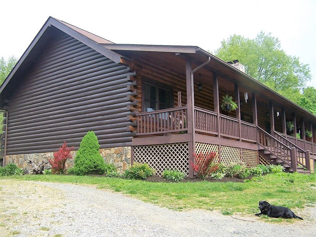 Customized Log Home on @6.5Private Acres in a Well-Established Neighborhood with Small Community Lake. Nicely Positioned on top of a Ridge @3200' Elevation with Beautiful Mtn and Lake Views from the Nearly 2000 sqft of Decks/Porches/and Patio. A few of the features include 4 or 5 BR/3.5 Ba, Open Floorplan with 16' Ceilings, All Hardwood Flooring on Main Level, Private Master Suite with Walk-In Closet, Dual Sinks in the Master Bath, and Large Glass Enclosed Sunroom.  Well-Appointed Kitchen with Custom Cabinetry, Newer Appliances, and Plenty of Counter-Top Space for the Chef in the Family.  Separate Laundry/Mud Room, Eat-In Breakfast Area, Large Family Room with Floor to Ceiling Stone Fireplace, 2 more Bedrooms, 1 Full and 1 Half Bath Round out the Main Level.  Downstairs you find a Full Finished Basement with 2 Bonus rooms for either extra Bedrooms, or Office, or Craft Room, or Whatever Suits your Needs.  There is also a Full Bathroom, a Den area, and Plenty of Customizable Flex Space.