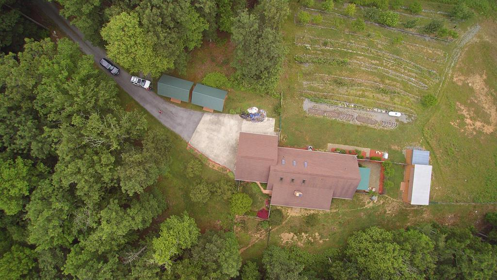 Home w/ Acreage Located in Blue Ridge Mountains. This 3 bedroom, 2 bath home located on 33.5 peaceful, tranquil acres has much to offer. The open concept living area has a cathedral ceiling and is spacious with lots of natural light and a fireplace. There are many different ways to configure this space. This home features several built in cabinets, an extra large, attached, 2 car garage, covered porches and a fenced in courtyard just off of the master suite. There is a whole house generator a leaf filter system, extra insulation in the attic. Everything here has been maintained well cared for. There is a fenced in front yard for pets and lots of mature landscaping and plantings around the home and outbuildings. There is a workshop with electricity in 4 sheds in the back of the house as well as two large sheds in front of house that could be used for studio space, storage or a workshop. 5 acres of open property are entirely fenced with a large graded area that could be ideal for a barn
