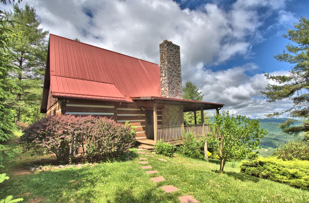 Cozy log cabin with fabulous views in Kindrick Mountain. This sweet 2-bedroom, 2-bath log cabin is located on a 13+ acre setting high on Kindrick Mountain in the Mouth of Wilson area of Grayson County. A partially covered deck wraps around 3 sides of the cabin offering plenty of space for outdoor relaxation, entertaining, & enjoyment of long range layered mountain vista views. A vaulted great room welcomes you inside to experience log cabin living in modern comfort. A stone wood-burning fireplace provides additional warmth on cool winter evenings and enhances the log cabin feel. In addition to the great room with the living, dining, and kitchen areas, the main level also offers a bedroom & full bath. The upper level features a loft area and a bedroom with full bath. The mountain setting features an abundance of wildlife and a diverse mixture of hardwoods, evergreens, & native mountain foliage.
