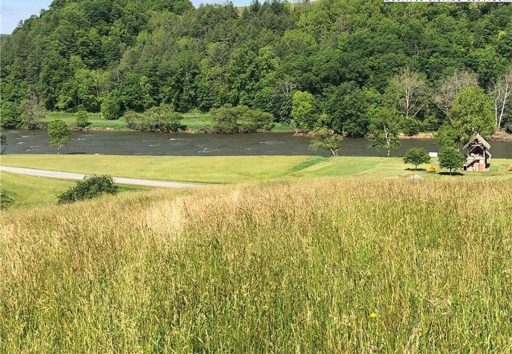 """Don't miss your opportunity to own 2.79 acres of prime real estate, situated on top of a knoll, overlooking the meandering New River with long range mountain views. Considered to be the """"BEST"""" lot in the River Meadows Community. Located just between Independence, VA & Sparta, NC. Your dream building site has a gentle slope. A paved access road leads to the upper portion of the lot, saving thousands of dollars establishing a driveway. The rolling acreage is a combination of woods & pasture, creating privacy but also an unobstructed gorgeous view! On the low lying land, there is a year round active spring running through. River Meadows boasts gently rolling terrain with a Public Water System, paved roads and underground utilities already in place. Enjoy over 26 acres of Common Area along the banks of the New River and then relax at the two level, log clubhouse featuring a full kitchen, covered outside seating and fire ring. This is it!"""