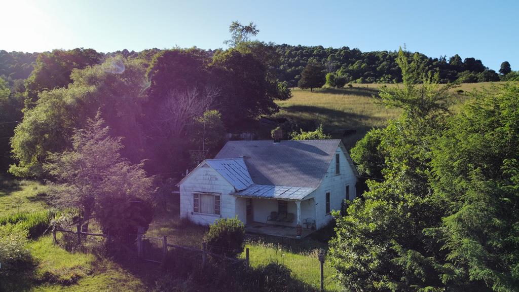 """This house is being sold """"As is-Where is""""  No repairs will be made by the owner.  This property has a bold spring on it.  There is a beautiful spot for building a home with a view. The property is suitable for a hobby farm."""