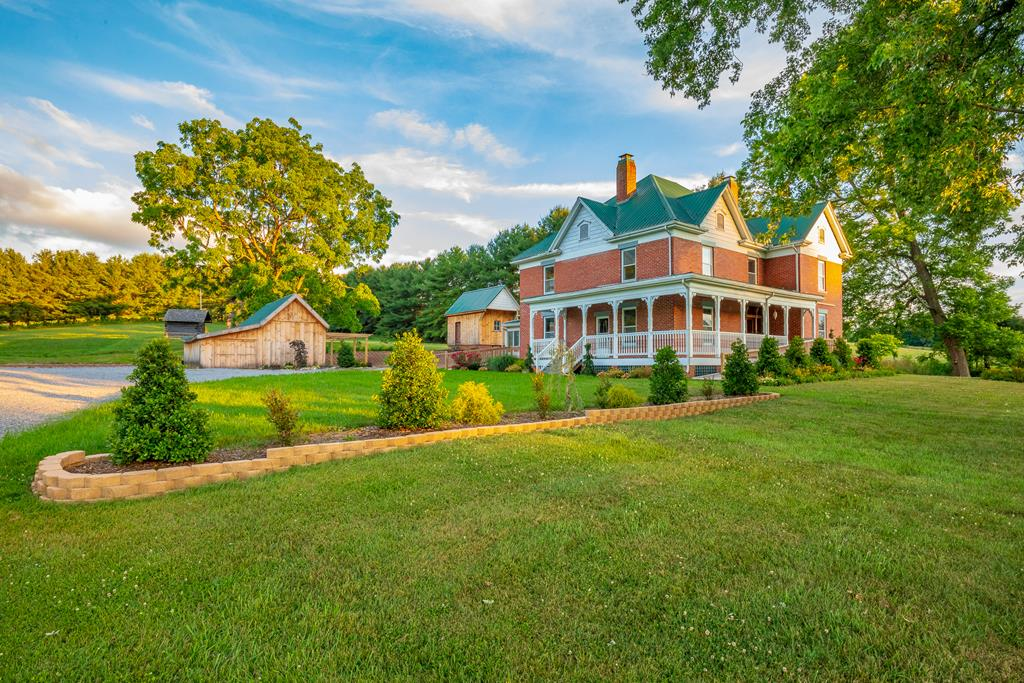 """The beautiful 2 story brick home that was built in 1911 sits on over 5 acres surrounded by lush green farms, breathtaking mountain views and less than 2 miles from I-81. The 5+ acre parcel is almost completely flat offering a wide array of possibilities. As you enter the home you are greeted by a grand staircase with a living room/library to your right and family room to your left, both with converging solid wood pocket doors. The family room has a hand painted mural """"Black Lick 1911"""". The master is on the main level and is accessible from the family room, hallway or master bath that also has a door to the hallway. The main level also has a formal dining, kitchen, laundry, mud and sun rooms. Upstairs is 4 large bedrooms, full bath, possible 2nd kitchen and sunroom with new exterior stairs. There are new wood ramps leading to the front porch and back door. The property also has a large workshop, several outbuildings, log cabin, smokehouse and new stone retaining walls. See 3D Tour."""