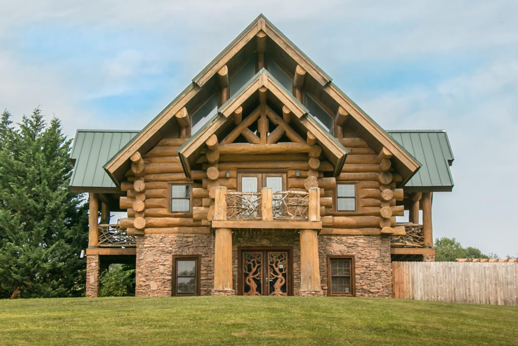 """STUNNING LOG CABIN HOME!!!! This home will """"wow"""" you the minute you step into the foyer!!  From it's lofty vaulted ceilings to the massive logs you will definitely want to see all this wonderful home offers.  Entering on the main floor you will find one or two bedrooms, (can be office and bedroom) plus, play room and two half baths.  You will be welcomed to the second floor by an oversized great room with a two story gas fireplace, master bedroom, full bath, dining area and a fabulous rustic kitchen with granite counter tops. Second floor also offers three cozy outdoor living spaces.  Use your imagination on the third floor, currently used as a bedroom.  Its very spacious and airy and over looks the second floor.  It could be used as a family room, office, playroom or theatre room.  The owners have just completed a privacy fenced area, great for children and pets. Also included is an out door building that could hold 10 plus cars.  There is an additional building site with great views."""