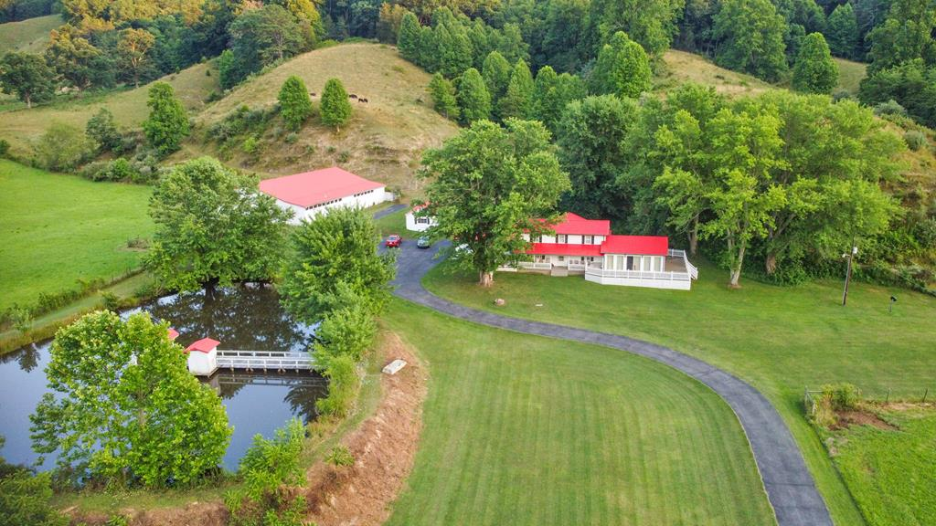 This magnificent three bedroom, three bath farmhouse sits on 254 +/- acres and has many amenities, including an incredible 7,000 square foot barn, a toolshed, spacious two car garage, and a creek running through the front portion of the property. With approximately 60 acres of open land and 194 acres of mature hardwoods with fencing throughout, the timber that is located on this beautiful property has not been cut in approximately 70 years. You can fish for bass and blue gill right from your front yard in the stocked pond with an attached dock and gazebo. This property is surrounded by mountains and astoundingly beautiful views from every angle. Looking for something out in the country with high speed internet? This property will have it! Point Broadband will be available in this area soon! What are you waiting for? Set up a showing to see this amazing property today!