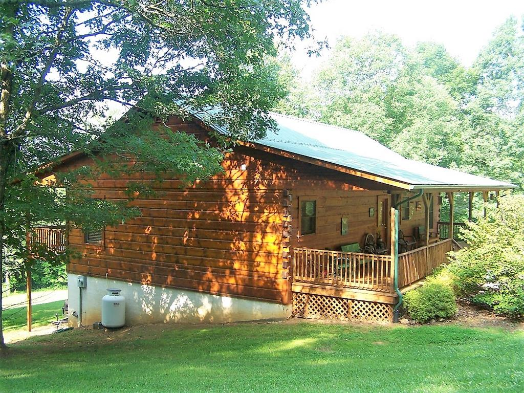 Immaculate, well maintained Log Home in the Mountains of Carroll County Va.  Very private setting on 10.6 Lush, Beautiful Acres.  A short hike down the hill takes you to the Creek frontage! Beautiful views and close to the town of Hillsville, the blue Ridge Parkway, and I-77 for convenience.   The Main Floor has 3 Bedrooms, an open Kitchen/Dining/Great Room with Vaulted Ceilings, Hardwood and Tile Floors, Gas Log Fireplace, Walk-in Closets in the Master Suite, a 10' x 48' Covered Deck on the Front and Back.  The finished Basement consists of Massive open area with Space for the whole family to hang out and gather to play games (Pool Table, Ping-Pong Table, and Air Hockey Table all Convey), plus a 3rd Full Bathroom and Large Laundry/Utility Room Round Out this Space.  Outside, there is a Fire Pit, an 11 x 16 Storage Building and Beautiful land that Reminds you of a Beautiful Park. The Driveway is Paved all the way to the house as well. All Appliances and Most Furniture Convey.