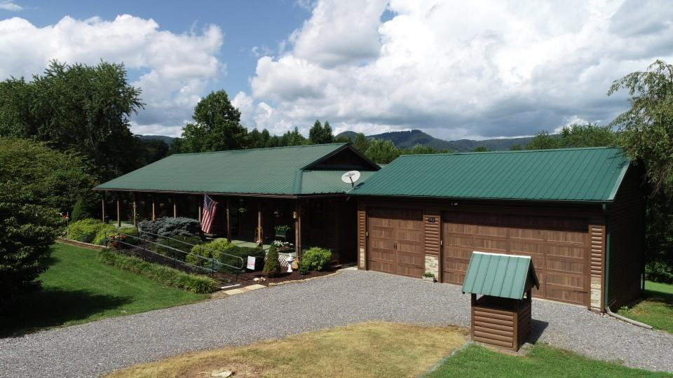 Tucked privately on paved country road just off Blue Ridge Parkway is this sprawling 3-4 bedroom, 2.5 bath log sided cabin ranch w/attached oversized garage plus full walkout basement on 2.57 acres. Property boasts everything to live, work, play, grow & sustain your family right here. 30x60 separate garage/workshop upfitted w/separate power, heated, water, two sided garage doors, fit 3-5 vehicles. The inground salt water pool is a perfect size for easy care fun in the sun for kids of all ages & surrounded by concrete pool deck, plus a pool cabana that joins the pool deck. The 3 season enclosed 11x16 screen porch screams for you to come sit a spell, chat for hours, toss steaks on the gas grill, which sits just off the dining room on the brand new 12' x 48' open deck. Everything here is resort living at its finest BUT its not a resort... ITS YOUR HOUSE... this home is ginormous inside. Double your living space & finish the 26x47 full walkout basement & fantastic GORGEOUS kitchen WOW!