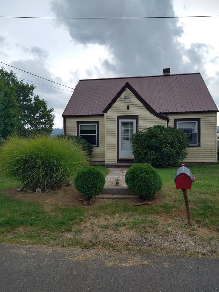 Nice little in-town home with beautiful mountain views from covered back porch!  Home was updated in 2009 with new roof, siding and insulated windows. Possible third bedroom upstairs with some finishing work. Home features original hardwood flooring and heat pump.  Open kitchen and dining area.  Great starter home or for those looking to be close to town amenities. Property being sold as-is/where-is.