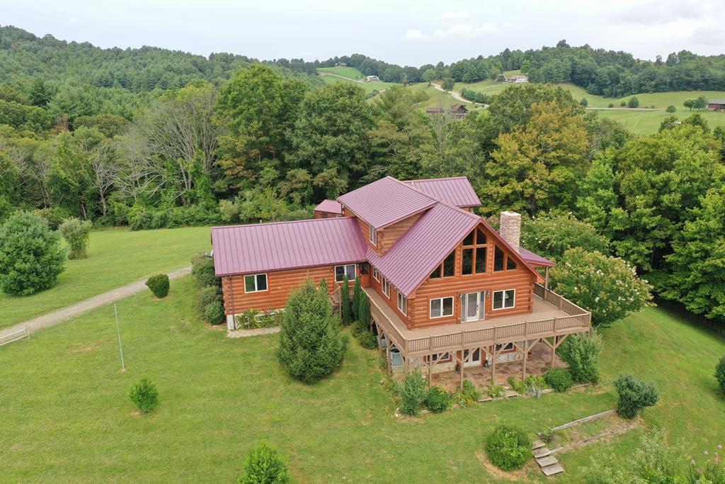Blue Ridge Mtn log cabin, w/views & open floor plan on 15 level to gently sloping acres at the end of Cul-de-sac in Crooked Creek Mt View Estates. Contemporary but Rustic 12 inch logs, custom built, 3 bedrooms, 3 and half bathes. Open, very spacious Great room with beautiful glass front, cathedral ceilings w/exposed interior beams, Log staircase and rails. Fabulous kitchen with custom cabinets, granite countertops, all major appliances including a double wall oven. Huge Master on suites w/ large walk in tile showers on both levels.  The full walk out, lower level offers a bedroom, full bath  separate den with a propane fireplace, bar, workout  and workshop area. Three bay attached garage with RV parking. Exterior amenities include wrap around porches, open decks, stamped concrete patio, a storage shed, fruit trees and a garden area. The views, the floor plan, the setting, the wildlife, the location close to the Crooked Creek wild life preserve and fee fishing area. This one has it all!
