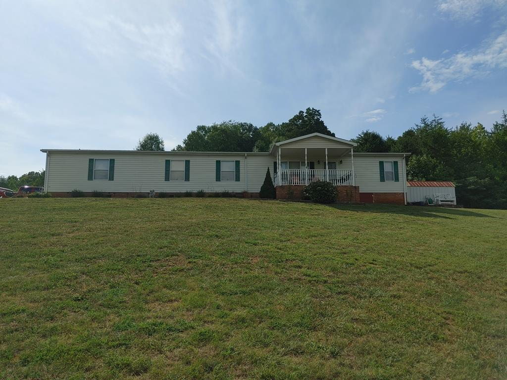 Very well maintained home on a nice open lot with views. Set on 1.61 acres. Has a spacious floor plan, gas fireplace, hardwood flooring. Large porch and rear deck. Also includes a storage building and barn with shed and power.