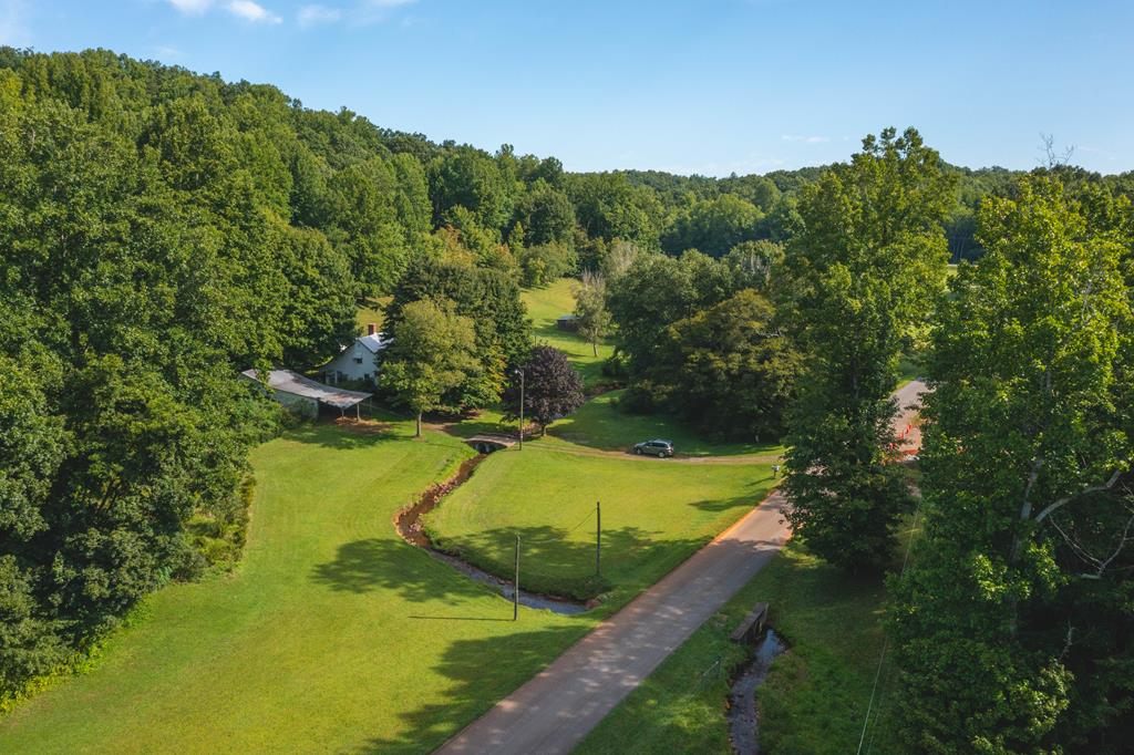 This 25 acres of beautiful rolling property is complete with cleared fields, wooded acreage, house and outbuildings, winding creeks. Cross the stone bridge to the 1942 Bungalow house which has a large original kitchen area, living, dining, bedroom and laundry on the first level. Second level has 2 bedrooms plus a sunny study or sitting area.  No improvements have been made to the house in many years, but the true value and attraction to this listing is the beautiful property which is approximately half wooded and half cleared, with a bold creek winding through the property and in front of the house.  Enter the driveway and cross the beautiful stone bridge to the home and approximately 12 acres of open yard and field with large run-in shelter or hay storage barn.  Perfect for horses or other livestock.  At the edge of the field where the woods begin, is a long row of Apiary boxes, making it a great location for an orchard with honey producing bee colonies.
