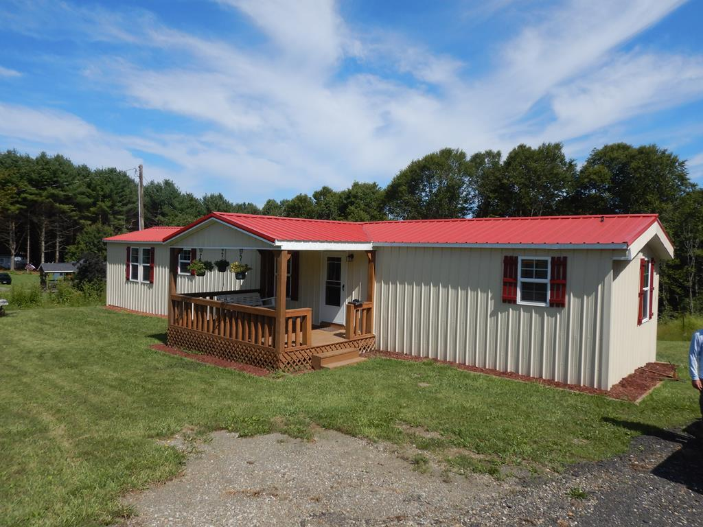 Nicely remodeled 2 bedroom, 2 bath manufactured home with central heat & cooling on one+ acre of land!  Great first home or vacation home opportunity in a quiet Woodlawn neighborhood that's just a few miles from outdoor activities and shopping in Galax and Hillsville, VA .  Only a 15 minute drive to the Blue Ridge Parkway!  This home has been fully remodeled inside and out with a new metal roof, metal siding, a covered front porch as well as a private covered rear deck & new vinyl windows throughout the home.  The  inside boasts a modern open concept kitchen area with ample cabinetry as well as new black and stainless appliances.  All the interior doors are solid wood and there is new drywall and paint throughout the home.  New hardwood and laminate wood flooring plus many more great improvements that you just have to see to appreciate!   Remodeled storage building on property.